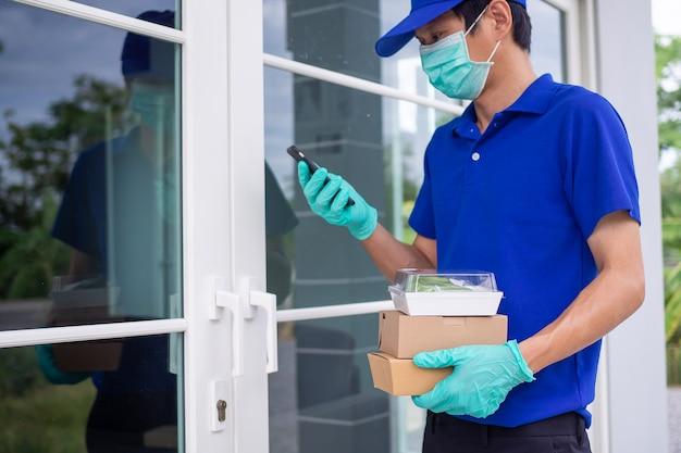 青いユニフォームとマスクを身に着けたアジア人男性配達員が、オンラインで注文する顧客に訪問販売のフードボックスを配達しています。