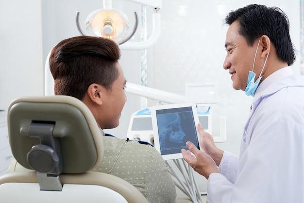 タブレットで患者に顎のx線画像を示すアジアの男性歯科医