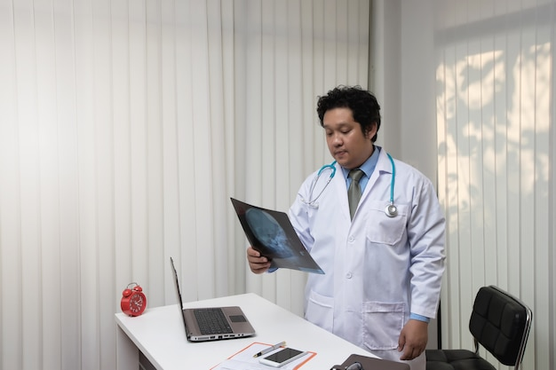Asian male doctor analyzing skull x-ray at desk