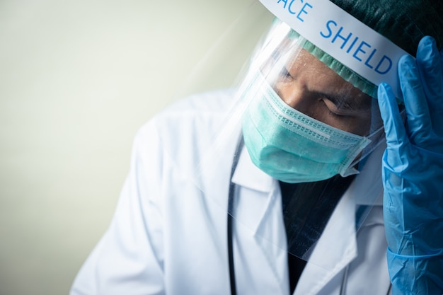 Asian male doctor wearing face shield and uniform with stethoscope