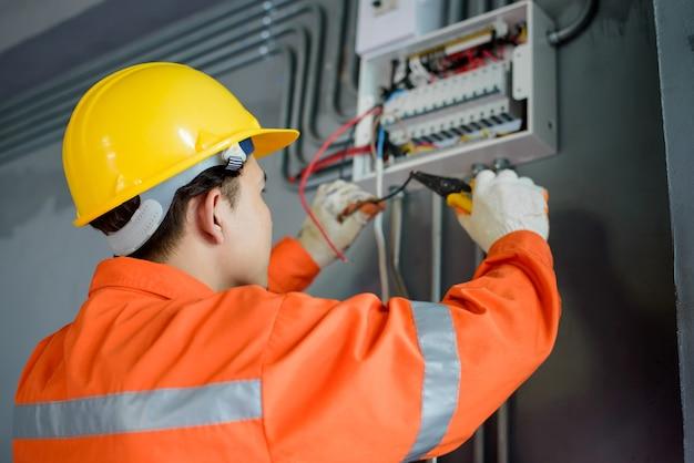 Электрики-мужчины из азии проверяют электрические системы в зданиях