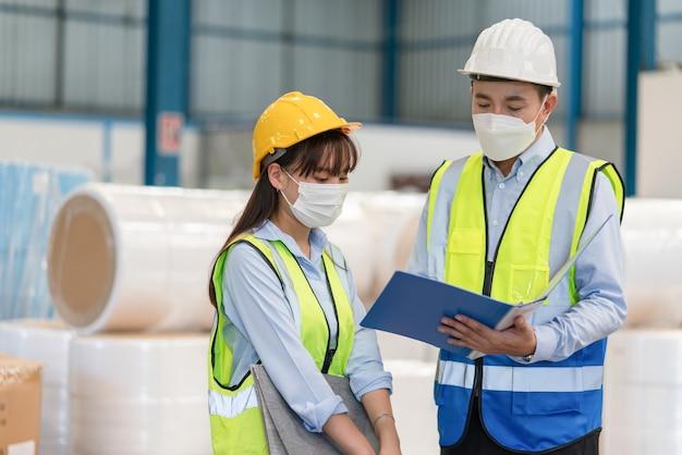 アジアの男性エンジニアが倉庫工場で女性技術者とのトレーニングを説明する文書を保持