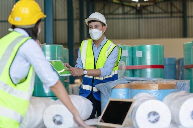 倉庫工場で製品をチェックしながらタブレットと画面上のポイントを保持しているアジアの男性エンジニア
