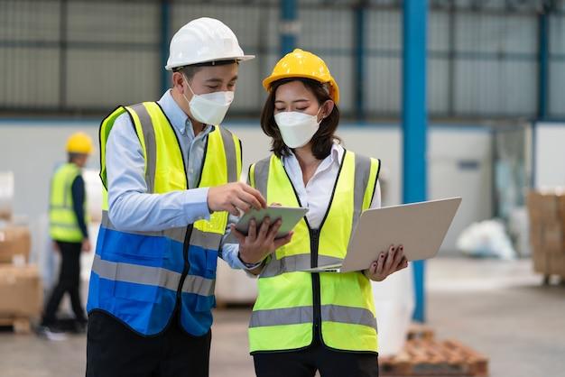 コロナウイルスを保護するためのヘルメット安全着用マスクのアジア人男性エンジニアが女性技術者と話し合う