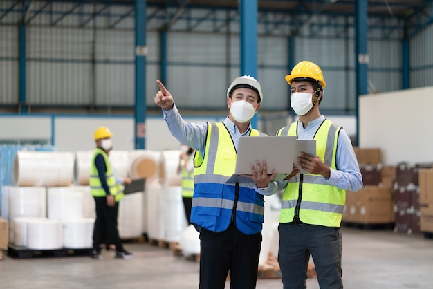 Asian male engineer wear mask to protect coronavirus point to storage location in warehouse factory
