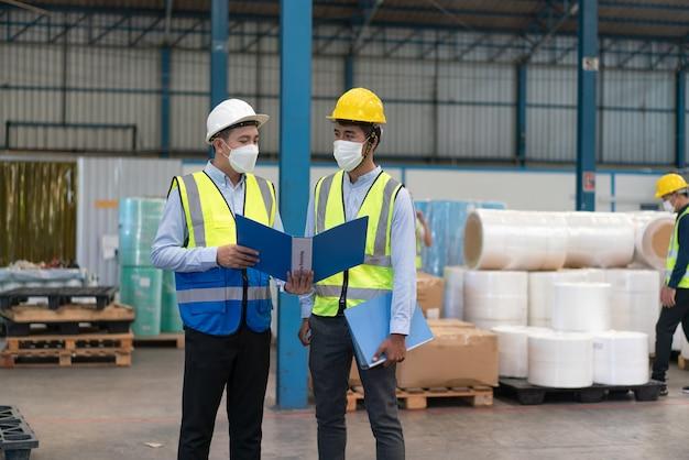 アジアの男性エンジニアの着用マスクがコロナウイルスを保護します文書は倉庫工場の労働者を説明します