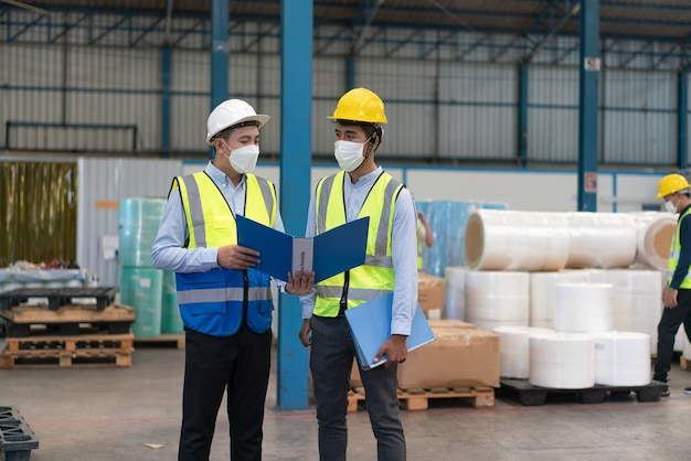 Asian male engineer wear mask protects coronavirus hold document explain worker at warehouse factory