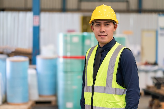Asian male engineer wearing safety vest and hardhat standing in warehouse factory industrial