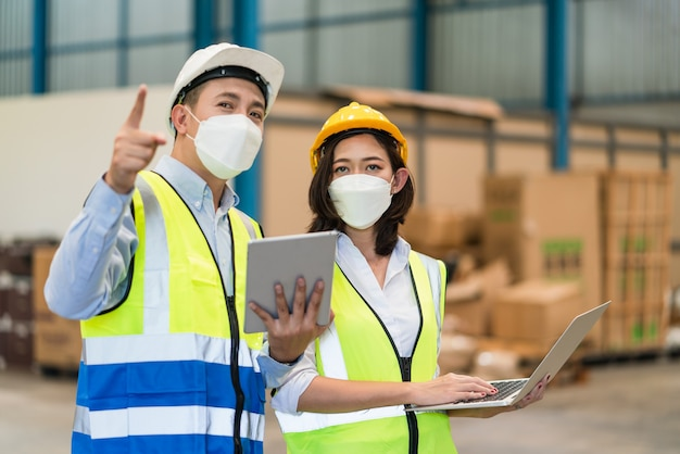 Asian male engineer with female technician hold laptop point to storage keep products in warehouse