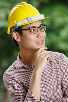 Asian male engineer with a yellow hard hat