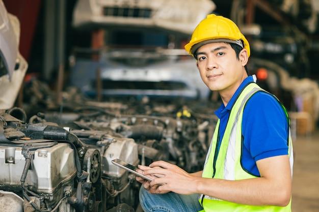 아시아 남성 엔지니어 작업자는 오래된 중고 자동차 엔진을 확인하기 위해 태블릿을 사용합니다.