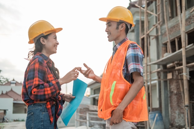 Asian male and female contractors discuss with hand gestures with the background of the unfinished building