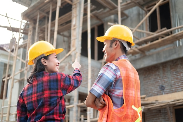 Asian male and female contractors discussing while pointing fingers