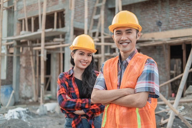 Asian male and female contractors standing with crossed hands smiling at the camera wearing safety helmets against the background of the unfinished building