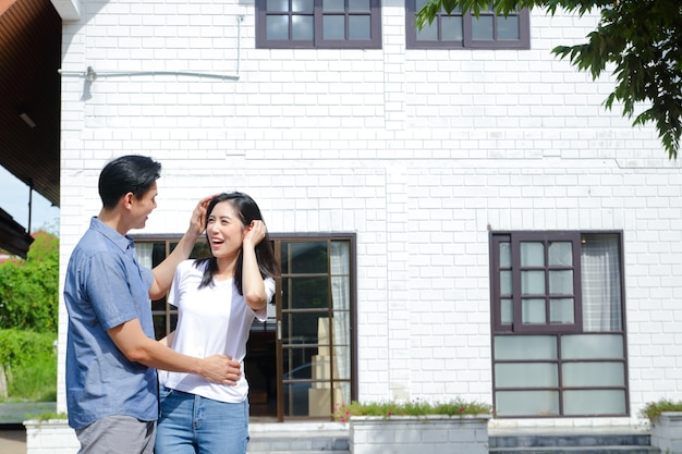 Asian male and female couples stand, hug, and smile happily in front of the new house. the concept of starting a married life in order to create a happy family. copy space