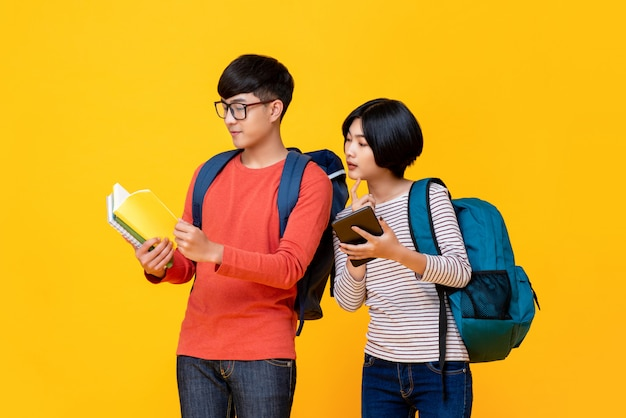 Asian male and female students looking at the book