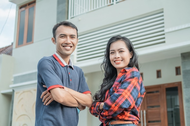 Asian male and female with crossed hands stands against a new home