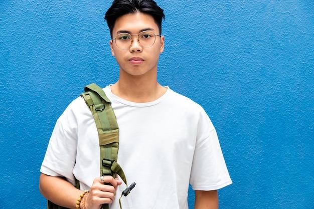 파란색 배경 복사 공간에 배낭을 메고 카메라를 바라보는 아시아 남자 고등학생
