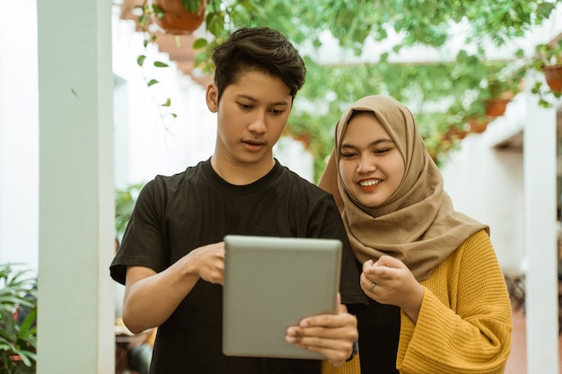 Asian male and hijab girl pointing to the screen of the tablet