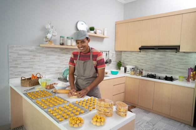 若い男のアジア人男性の自家製ケーキの肖像画は、プラスチックの箱にnastarケーキを置きます
