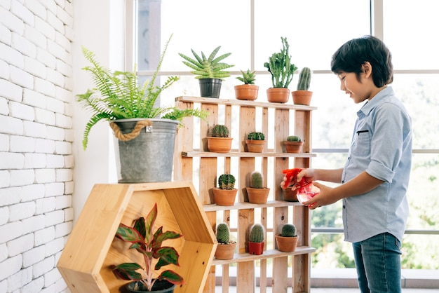 An asian male kid enjoys taking care of the plants by watering by water sprayer in an indoor houseplant at home.
