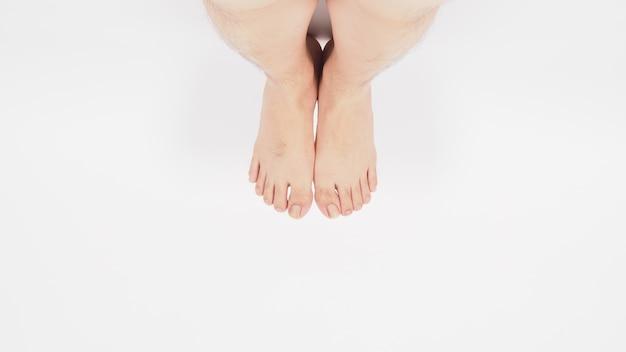 アジア人男性の脚と裸足は白い背景で隔離されます