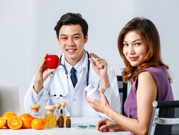 Asian male medical practitioner and female patient smiling and looking at camera while advertising fruits and vitamins in clinic
