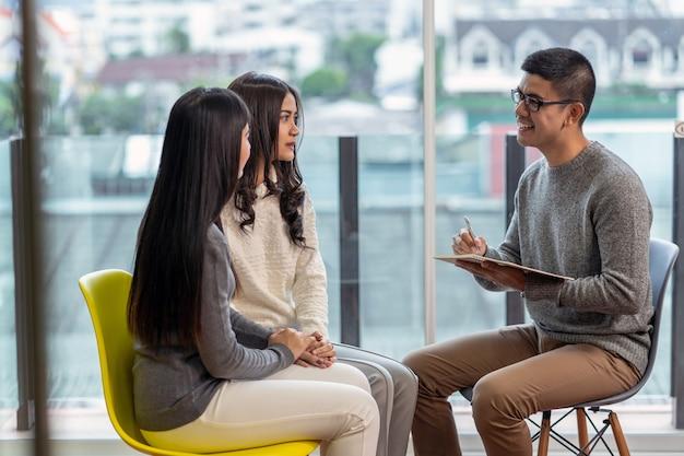 Азиатский мужской профессиональный психолог доктор дает консультации пациентам-лесбиянкам