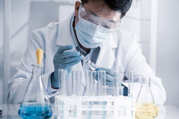 研究室で働くアジアの男性科学者。ワクチン開発のコンセプト。