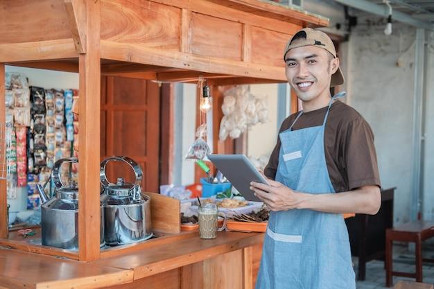 カートの屋台の横に立っているタブレットpcを保持しているエプロンのアジアの男性の売り手
