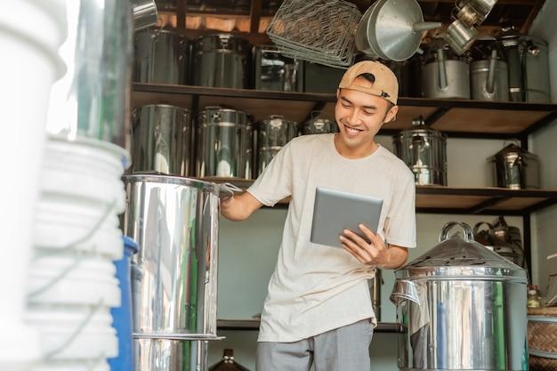Азиатский продавец-мужчина стоит возле большой сковороды, используя планшет для проверки интернет-магазина в магазине бытовой техники