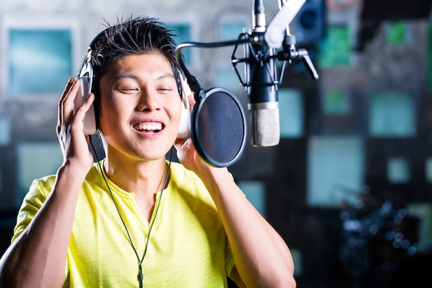 Asian male singer producing song in recording studio