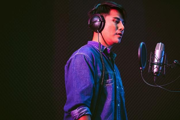 スタジオマイクとマイクのポップシールドを使用して曲を録音するアジアの男性歌手