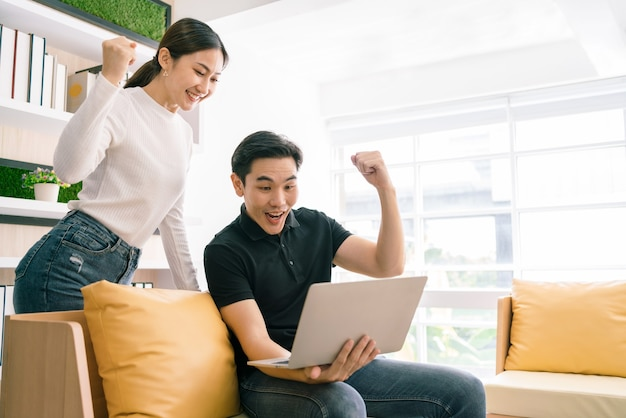 Asian male sitting and female standing back of him while working, feel happy and excited from a laptop. businessman working on laptop at home.