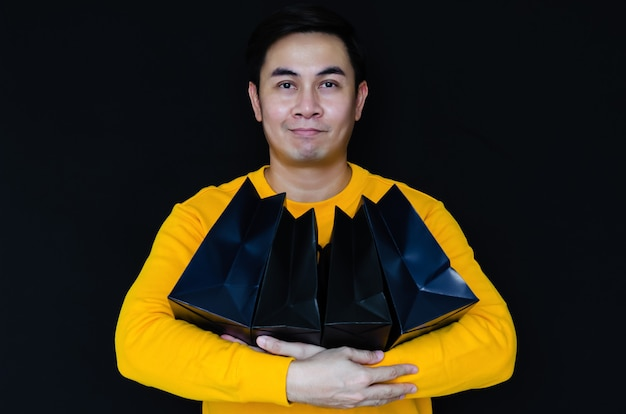 ブラックフライデーのコンセプトの暗い背景に笑顔とショッピングバッグを保持しているアジア人男性。