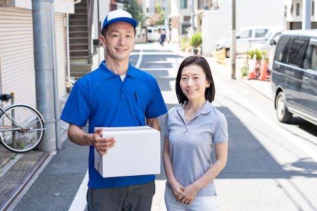 荷物を運ぶアジア人男性スタッフと屋外の女性客
