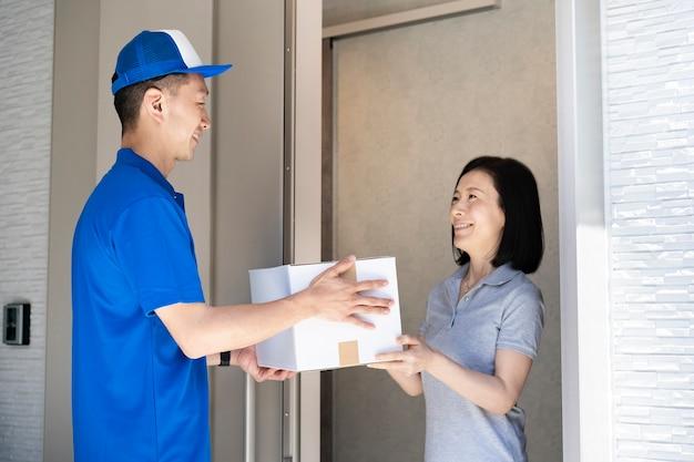 荷物を渡すアジア人男性スタッフと受け取る中年女性