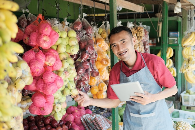 Asian male stall owner smiles while holding a digital tablet looking at the camera while holding