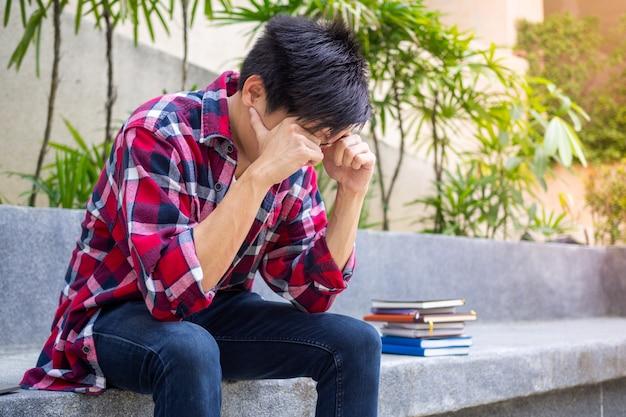 Азиатские студенты мужского пола, сидящие взволнованно подчеркнуты, о неудачных результатах экзамена.