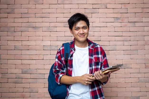 アジアの男子学生は格子縞のシャツを着ています。レンガの壁の横に立って、バックパックを運んで、本、学用品を運んで、勉強の準備をして、笑顔で。