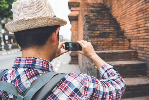 Asian male tourist backpacker taking photo with smartphone at tha phae gate, one of the ancient famous landmark of the city in chiang mai thailand