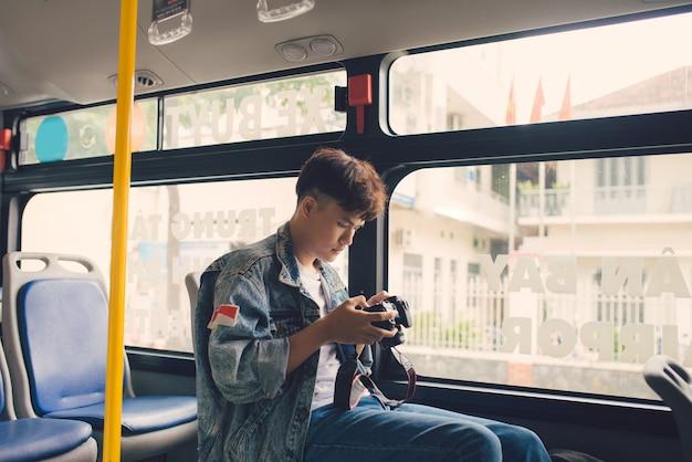 버스 창에서 도시를 촬영하는 아시아 남성 관광객