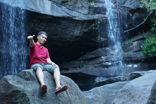 Азиатский мужской туристический водопад фон