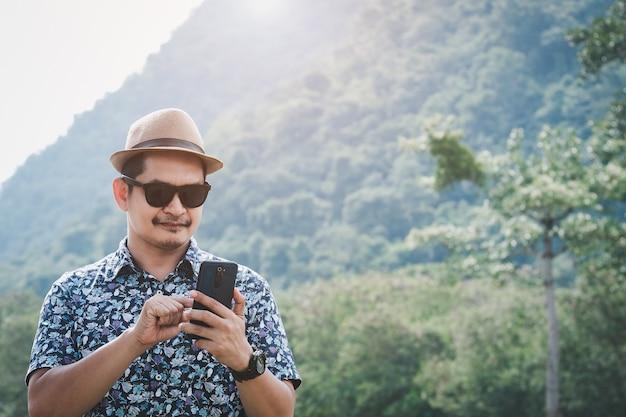아시아 남성 관광객들은 휴일 동안 즐겁게 스마트폰을 사용합니다. 모험 관광 및 기술의 개념
