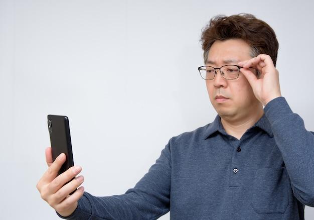 Азиатский мужчина пытается прочитать что-то на своем мобильном телефоне. плохое зрение, пресбиопия, миопия.