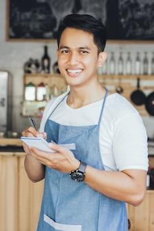 Азиатский мужчина официант в порядке написания фартук