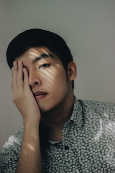 그의 손으로 그의 눈을 덮고 버튼 업 셔츠를 입고 아시아 남성