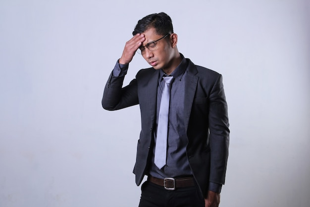 An asian male worker feeling exhausted and having headache