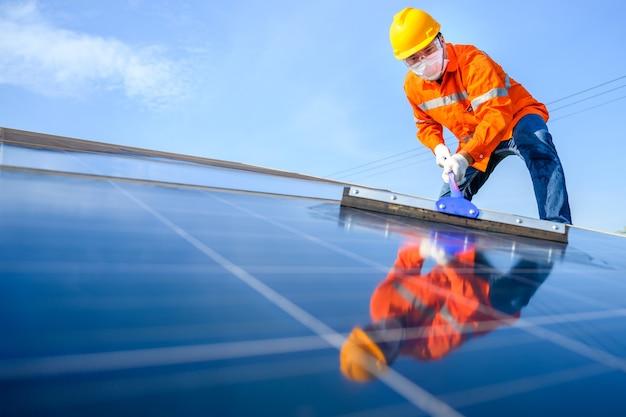 Азиатский рабочий или инженер-мужчина на солнечной электростанции солнечная панель очищается с помощью швабры. на солнечной электростанции.