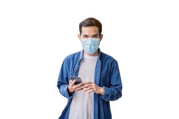 アジア人男性携帯電話のライフスタイルを保持しているフェイスマスクを身に着けている新しい通常の社会的距離